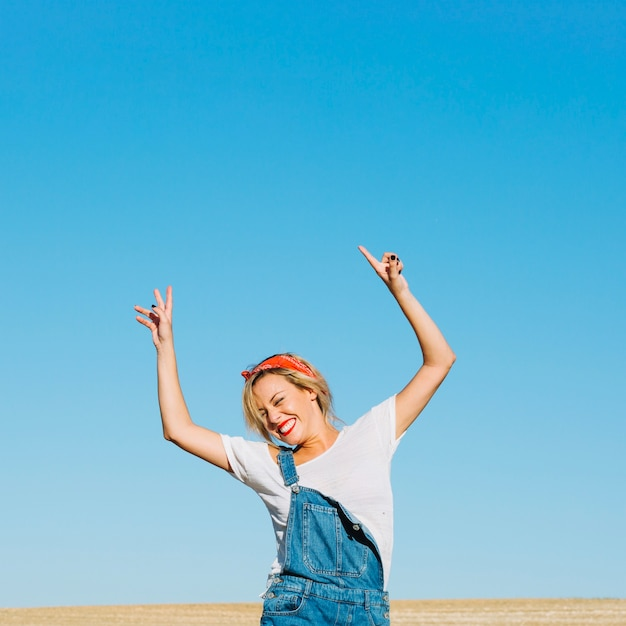 Cheerful woman posing in field Free Photo