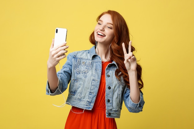 Cheerful woman posing while photographing herself on smart phone camera for chat Premium Photo