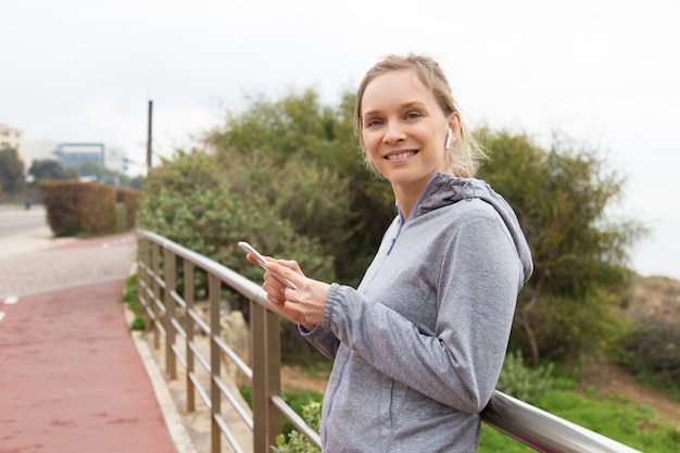 Cheerful woman runner choosing music for outdoor training Free Photo