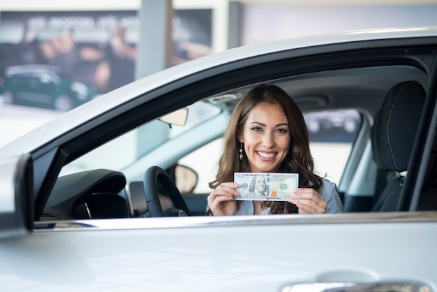 Cheerful woman sitting in the new car holding us dollar banknote Free Photo