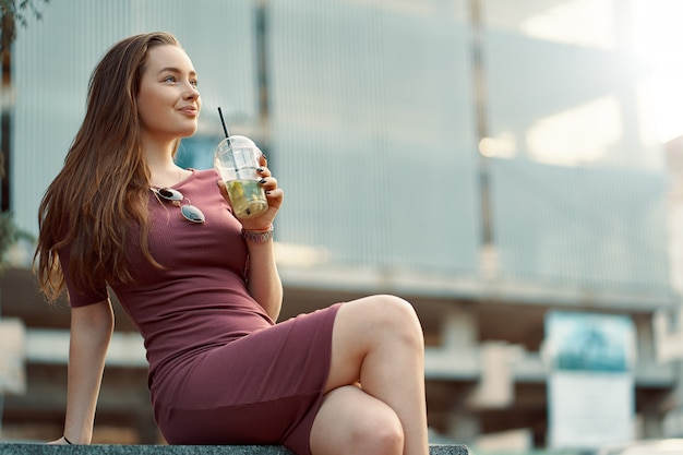 Cheerful woman in the street drinking morning refreshing drink Free Photo