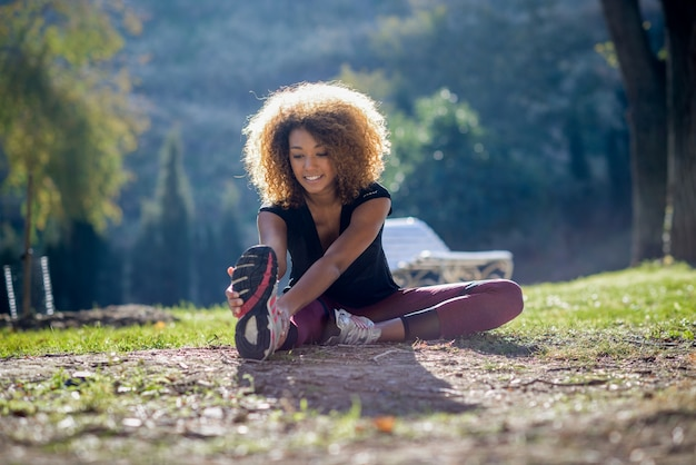Cheerful woman stretching her leg on the ground Free Photo