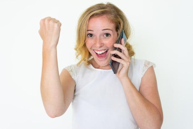 スマートフォンで話していると成功を祝っている陽気な女性 無料写真