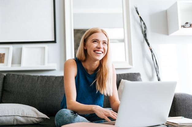 ラップトップを使用して、家で笑っている陽気な女性 無料写真
