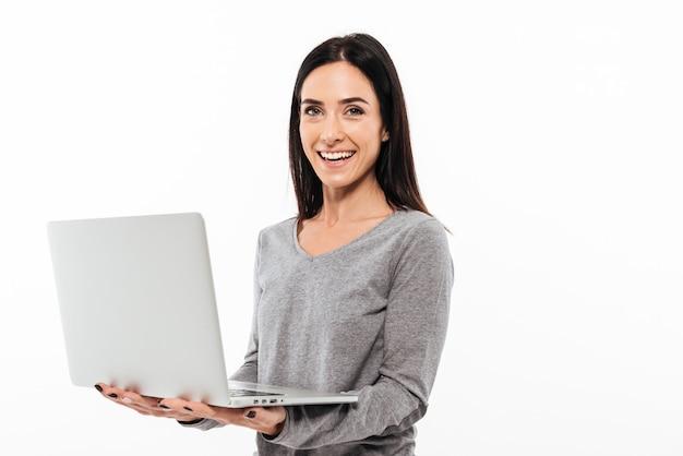Cheerful woman using laptop computer. Free Photo