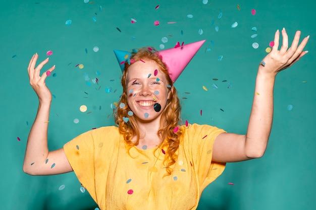 Cheerful woman wearing two birthday cones Free Photo