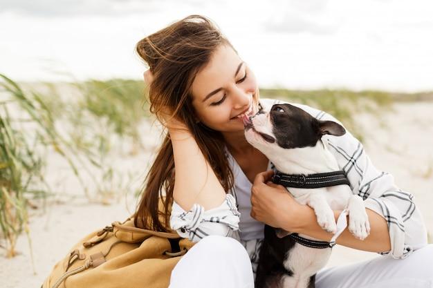 Donna allegra con cane carino boston terrier che gode del fine settimana vicino all'oceano. Foto Gratuite