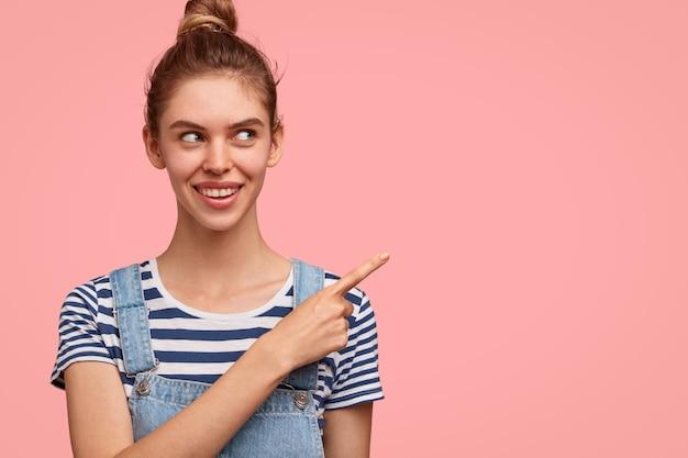カジュアルな服装で、髪のお団子を持つ陽気な女性 無料写真