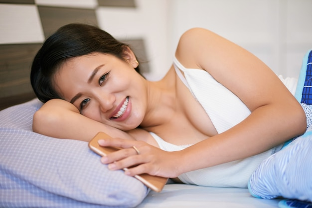 Cheerful woman with phone lying in bed Free Photo