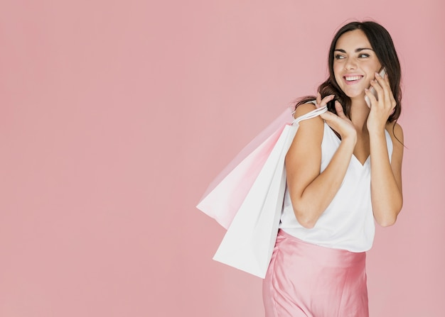Cheerful woman with shopping bags looking back Free Photo