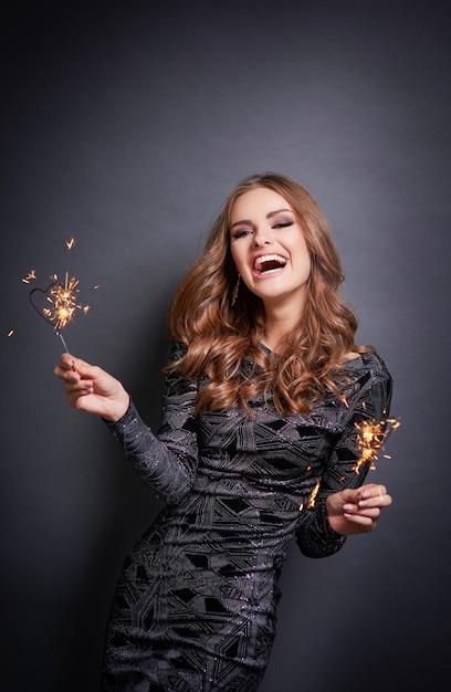 灰色の壁で笑っている線香花火と陽気な女性 無料写真