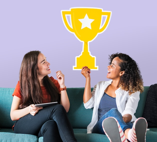 Cheerful women holding trophy icon Free Photo