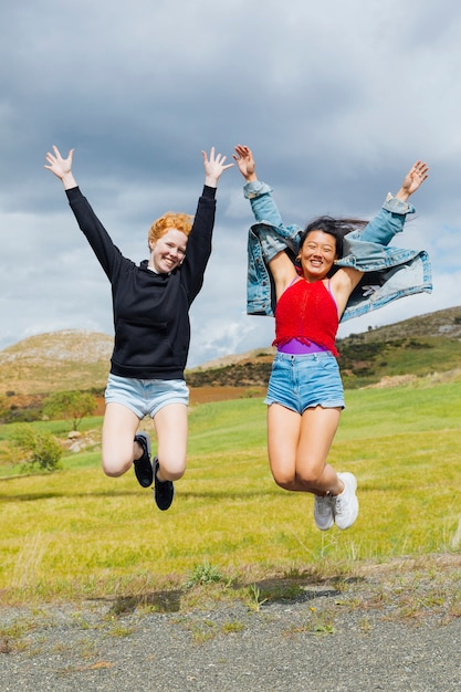 Cheerful women jumping on roadside Free Photo
