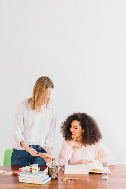 Веселые женщины, обучающиеся вместе за столом Бесплатные Фотографии