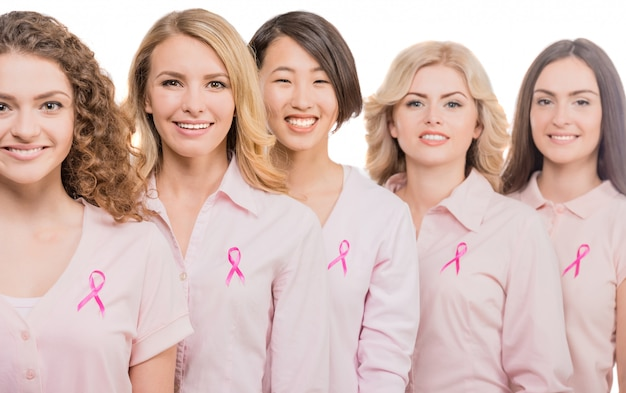 Cheerful women wearing pink ribbons to support breast. Premium Photo
