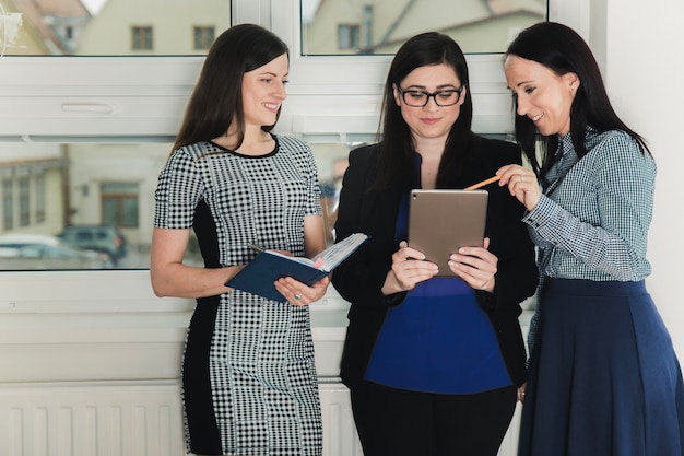 Cheerful women with tablet in office Free Photo