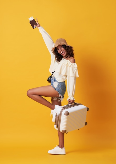 Cheerful young african woman dressed in summer clothes holding passport with money Premium Photo