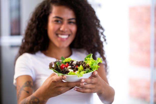 가정 부엌에서 야채 샐러드를 먹는 쾌활한 젊은 아프리카 미국 여자 프리미엄 사진