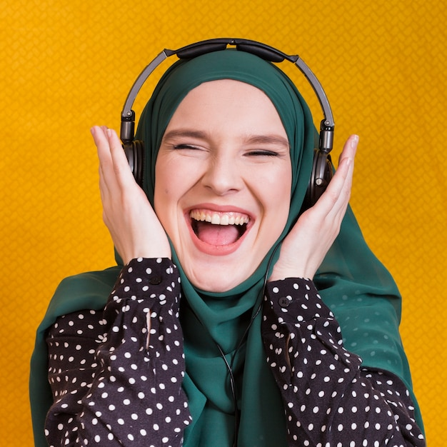 Cheerful young arabian woman listening music on headphone against yellow background Free Photo