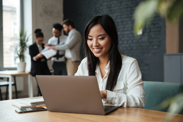 Cheerful young asian businesswoman using laptop Free Photo