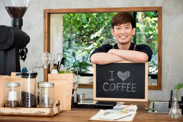 Cheerful young asian man entrepreneur at counter in coffee shop Premium Photo