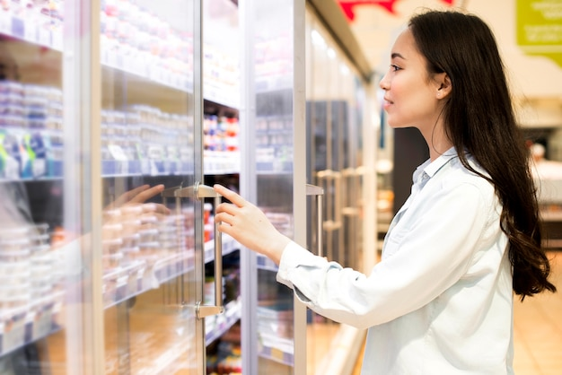 Cheerful young asian woman choosing dairy products at supermarket Free Photo