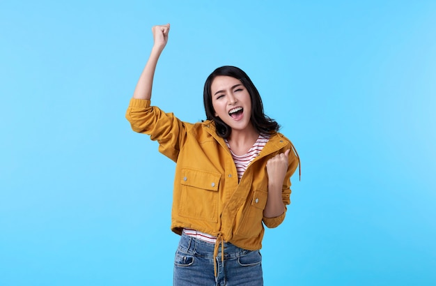 Cheerful young asian woman raising his fists with smiling delighted face, yes gesture, celebrating success on blue background. Free Photo