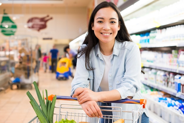 Cheerful young asian woman with shopping cart at supermarket Premium Photo