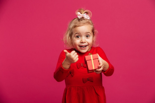 Cheerful young blonde girl in red dress holding gift box Free Photo