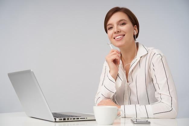 Allegro giovane donna dai capelli corti dagli occhi castani con trucco naturale che sorride sinceramente mentre è seduto in ufficio con il computer portatile e che effettua chiamate con auricolare, isolato su bianco Foto Gratuite