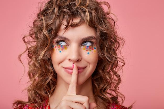 Allegro giovane bruna signora riccia con punti multicolori sul viso che osserva da parte con un sorriso affascinante e mantenendo l'indice sulle labbra, isolato Foto Gratuite