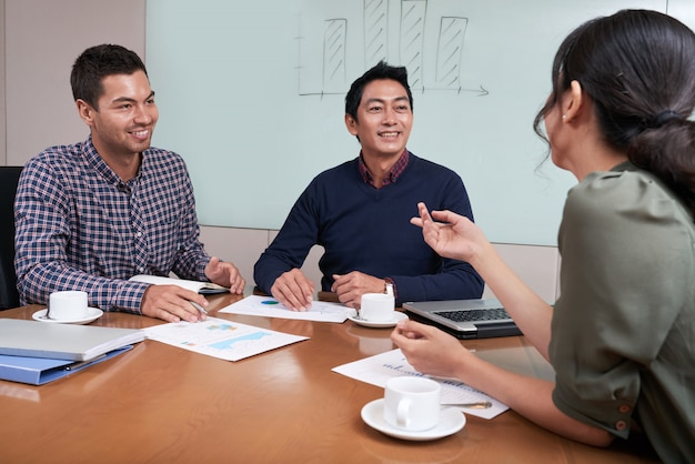 Cheerful young business people having brainstorming session Free Photo