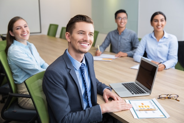 Cheerful young businessman sitting at seminar Free Photo