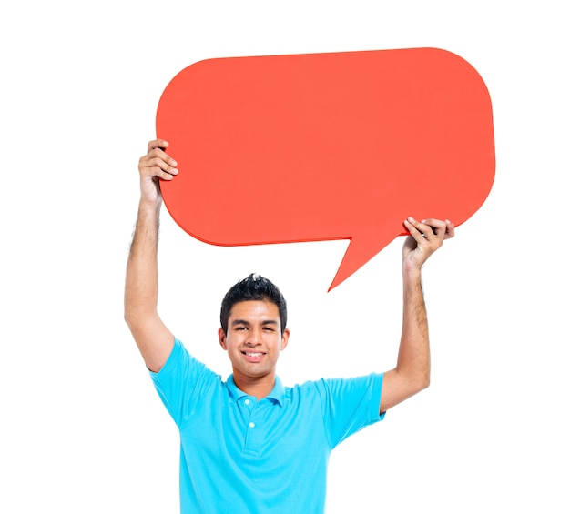 Cheerful young casual man holding speech bubble Free Photo