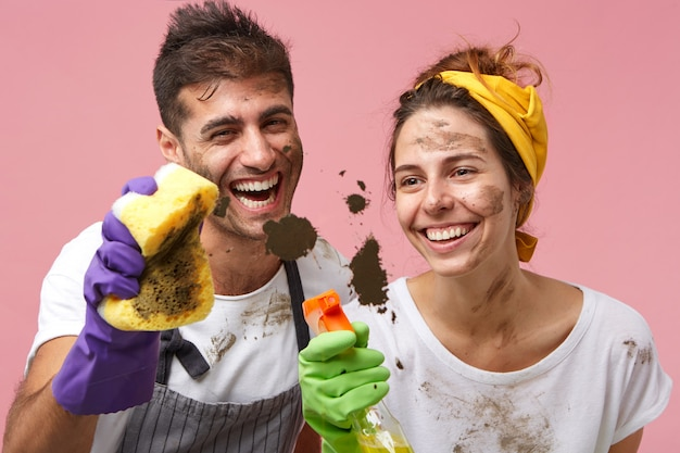 一緒に家を掃除する汚い顔で陽気な若い白人カップル。きれいな女性と夫の両方を笑顔で保護手袋をはめ、クリーニングスプレーとスポンジを使用してウィンドウを洗う 無料写真