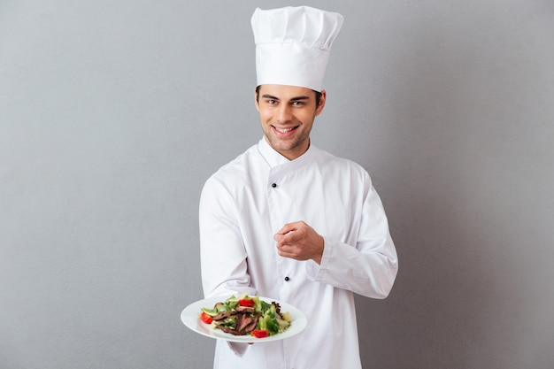 Cheerful young cook in uniform holding salad pointing to you. Free Photo