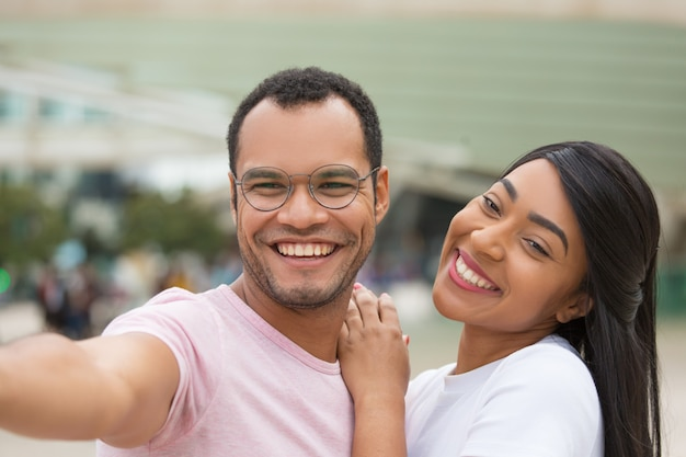 Cheerful young couple posing for selfie on street Free Photo