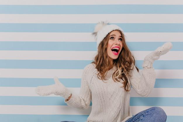 白い服とブルージーンズの陽気な若い巻き毛の女の子モデルは床に座って、縞模様の青い壁に肖像画のために感情的にポーズをとっています 無料写真