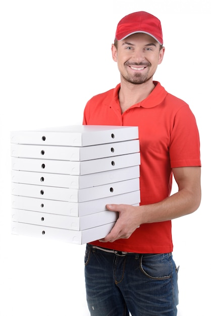 Cheerful young deliveryman holding a pizza box. Premium Photo
