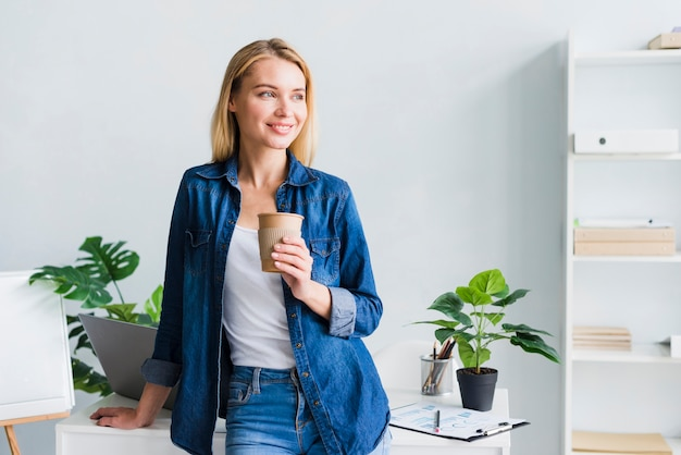 Cheerful young female holding paper cup on break at work Free Photo
