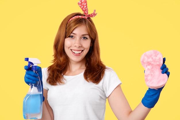 陽気な若い女性の家政婦はカジュアルなtシャツとヘッドバンドを着て、ほこりをきれいに行く、洗浄スプレーとスポンジを保持しています。 無料写真