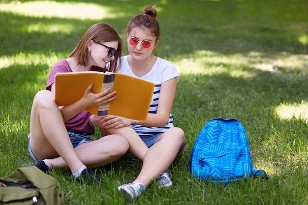 本で面白いものを読みながら陽気な若い女性が喜んで笑う、彼女の親友の近くに座っています。 Premium写真