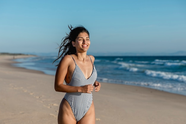 Cheerful young female running along seaboard Free Photo