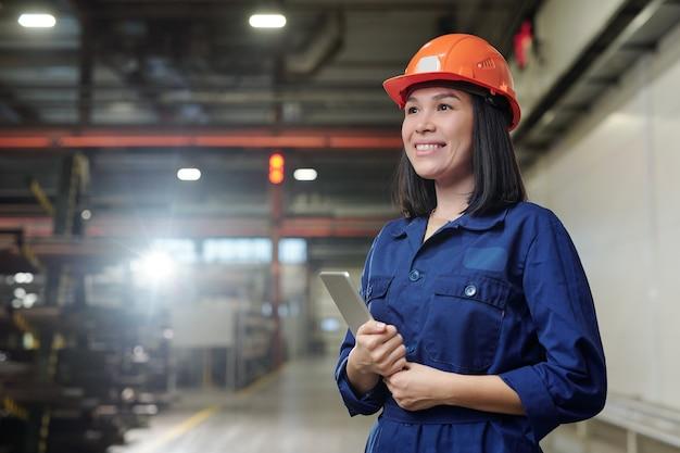 작업 과정을 제어하는 동안 산업 공장의 작업장에 서있는 터치 패드와 쾌활한 젊은 여성 Wngineer 프리미엄 사진