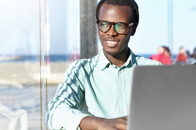 Allegro giovane libero professionista in un cappello alla moda e occhiali che sorridono felicemente Foto Gratuite