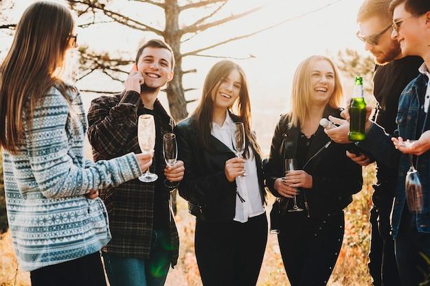 Веселые молодые друзья улыбаются и пьют пиво и шампанское, стоя в прекрасной сельской местности вместе Premium Фотографии