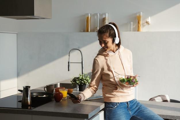 Веселая молодая девушка слушает музыку в наушниках на кухне дома, ест салат из миски Premium Фотографии