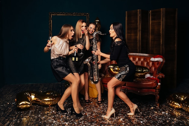 Cheerful young girls dancing and drinking champagne while their girfriend playing Free Photo