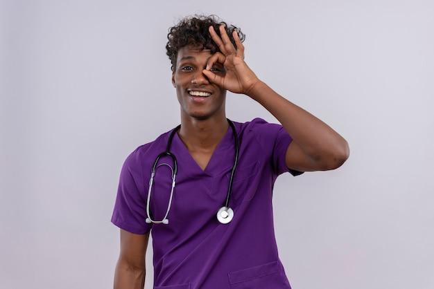 A cheerful young handsome dark-skinned doctor with curly hair wearing violet uniform with stethoscope peeking through a hole formed with his thumb and index finger Free Photo