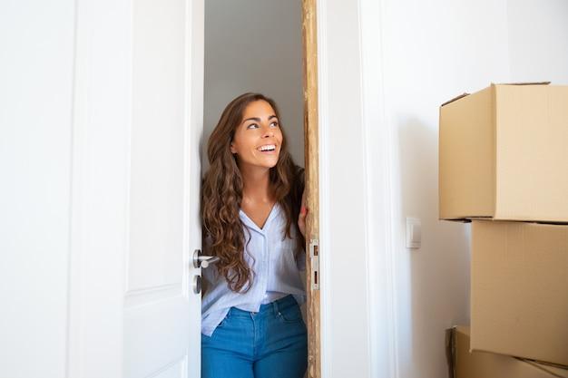 쾌활한 젊은 히스패닉 여자 새 아파트로 이동, 문을 열고, 출입구에 서서, 판지 상자의 스택을보고 웃고 무료 사진